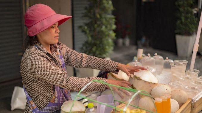 Kobieta sprzedaje sok z kokosow w Bangkoku